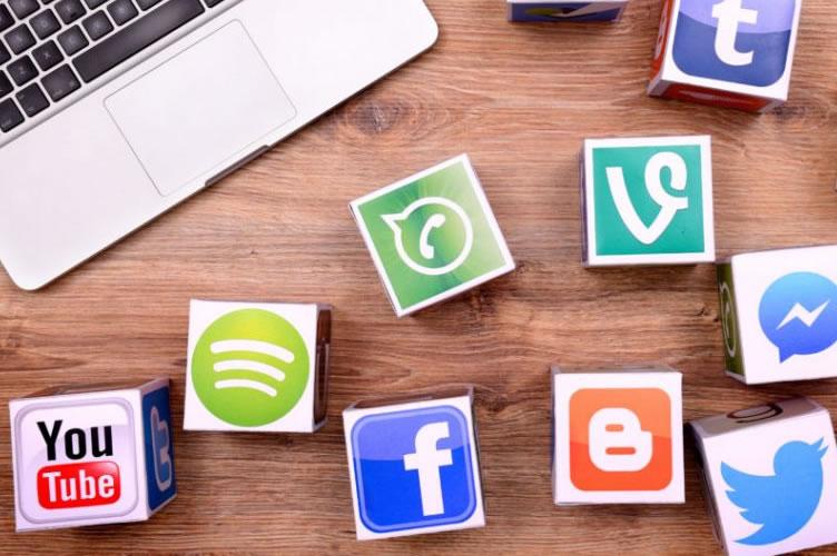 notebook na mesa com diversos blocos com a logomarca de todas as mídias sociais.