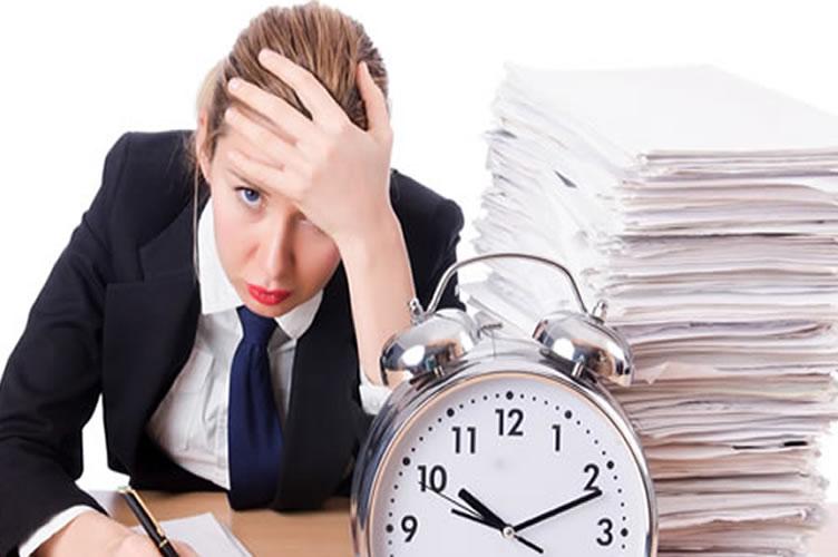 A corretora de imóveis em uma mesa, super cansada com o tempo correndo contra ela e atolada de papeis. O gerenciamento de tempo no mercado imobiliário faz parte da carreira do corretor.