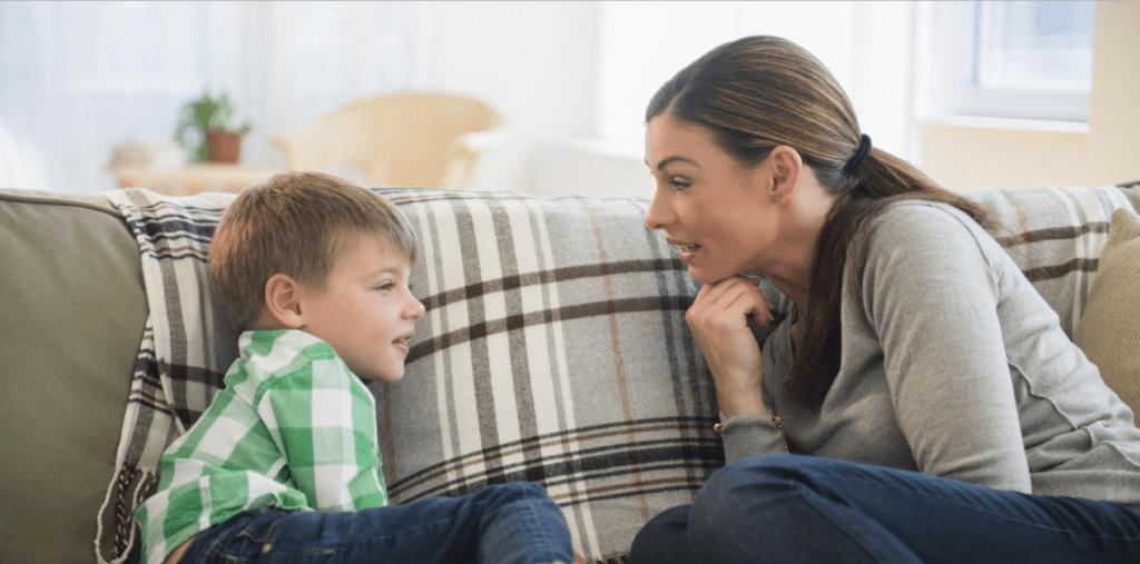 Uma mulher, gerente de locação de imóveis aprendendo com seu filho. No sofá