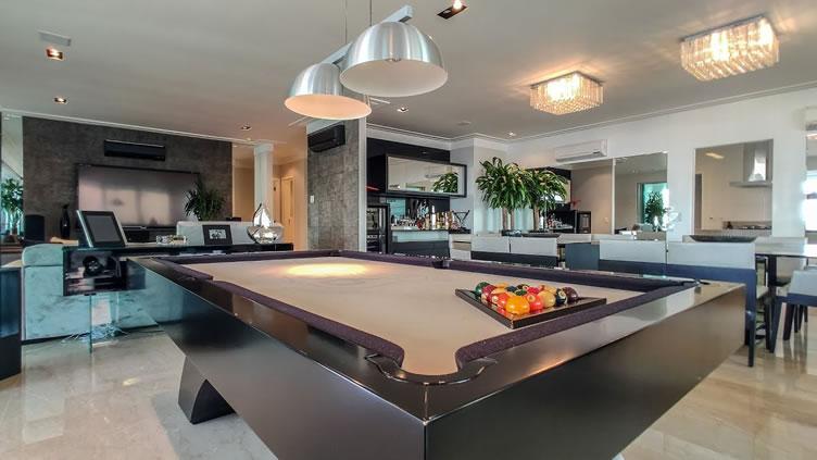 Sala super tecnológica com mesa de sinuca em um imóvel de luxo.