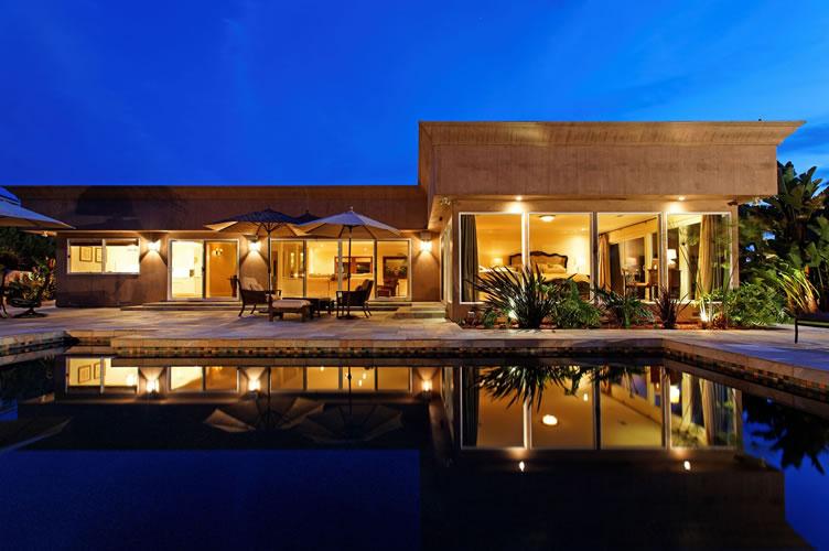 Imóvel de alto padrão. Uma linda casa com piscina na frente no fim de tarde.