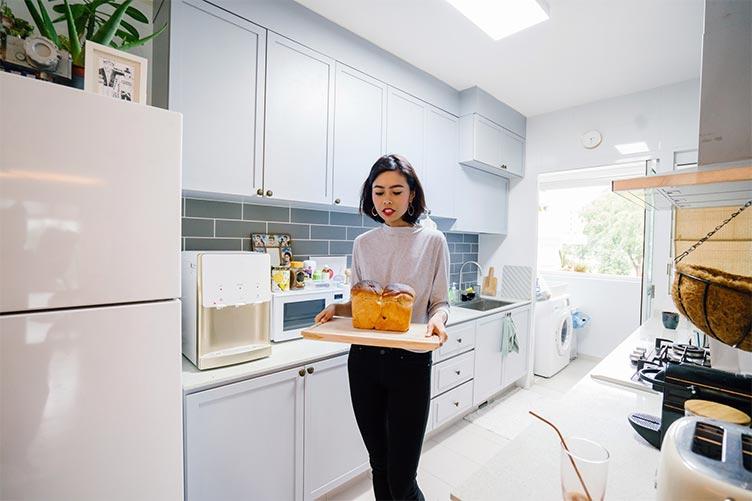 Mulher servindo o pão caseiro em uma bandeja na cozinha organizada e limpa.