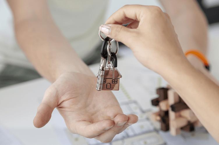 corretor de imóveis entregando as chaves da casa nova de um cliente satisfeito.