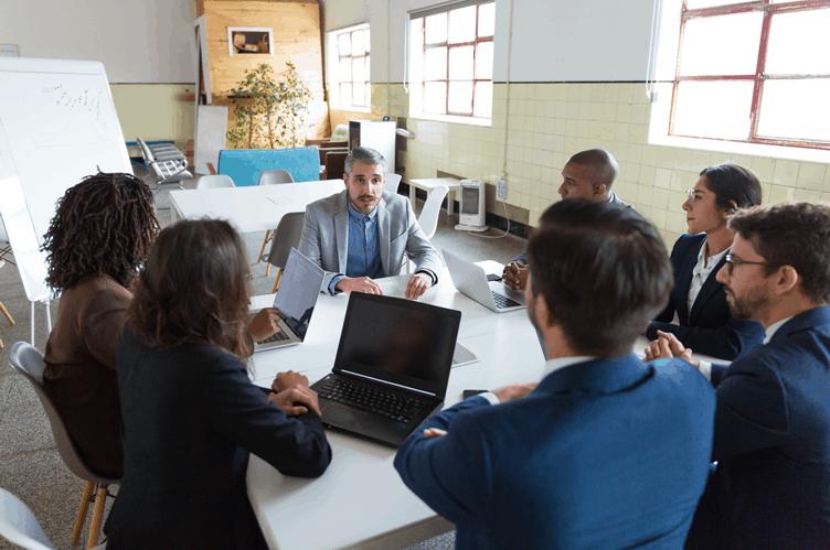 líder da equipe imobiliária em reunião com os corretores de imóveis sentados em volta de uma mesa com computadores para trabalhar a satisfação profissional.