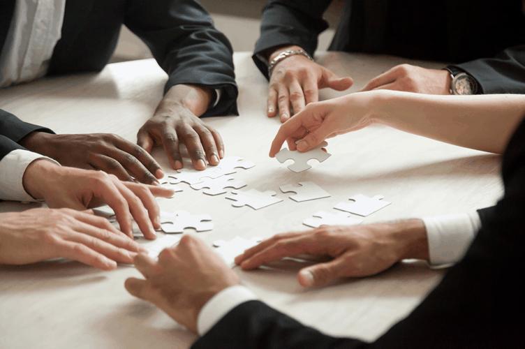 Mãos de corretores de uma equipe imobiliária resolvendo conflitos com ajuda do lider que os lidera