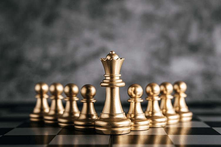 Peças de Xadrez em Ouro com a Rainha na frente para liderar uma equipe imobiliária.