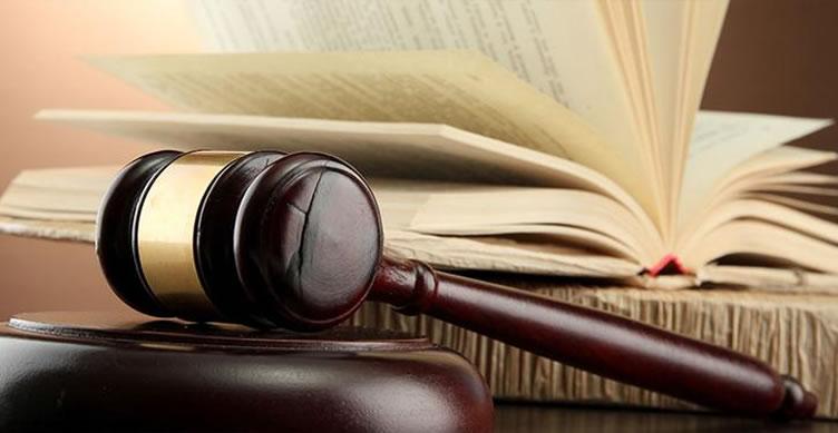 Martelo de um juíz e um livro de leis atrás.