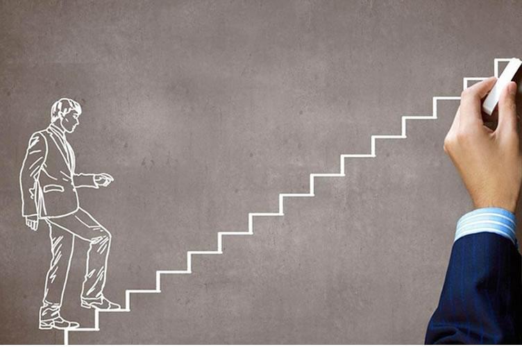 Corretor de imóveis escrevendo a giz em um quadro negro sua estratégia para marketing de midias sociais da imobiliária. No quadro está desenhado uma escada com ele mesmo subindo a pouco os degraus.