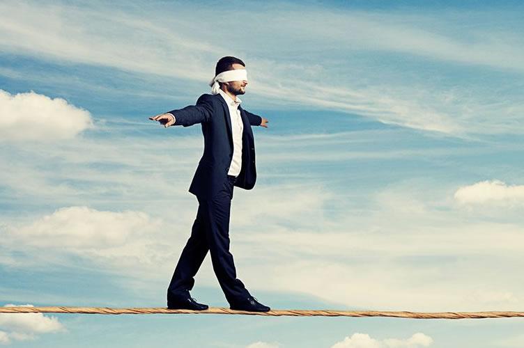 Corretor de imóveis exercendo sua confiança. Andando vendado sobre uma corda bamba. Ao fundo o céu, para dar a impressão de altura.