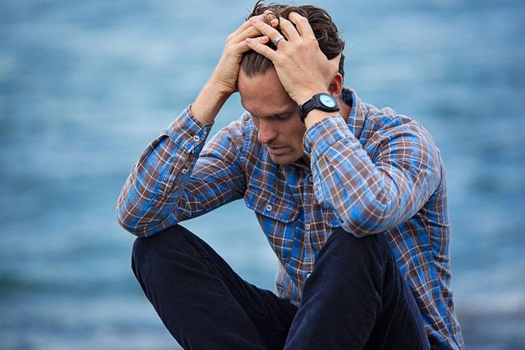 Gerente da imobiliária em momento de stress. Sentando ao chão e passando a mão aos cabelos.