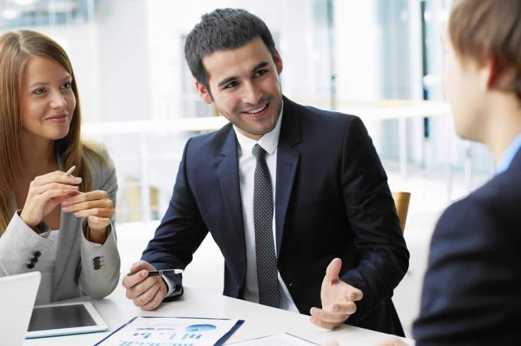 O gerente de uma imobiliária de sucesso conversando em tom amigável com dois corretores. Uma mulher de cabelos ruivos e um homem de cabelo loiro. O gerente está bem vestido e sorrindo.