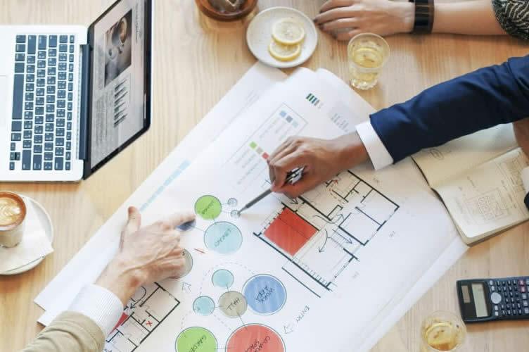 Notebook, cafés e um projeto. Um bom gerente de uma imobiliária precisa ser diligente. Na imagem mostra uma reunião, com a mão de um gerente dando explicações e delegando funções.