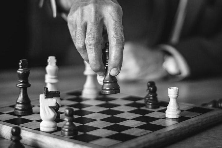 Homem movendo uma peão em um tabuleiro de xadrez. Planejamento sempre foi a alternativa mais segura na vida.
