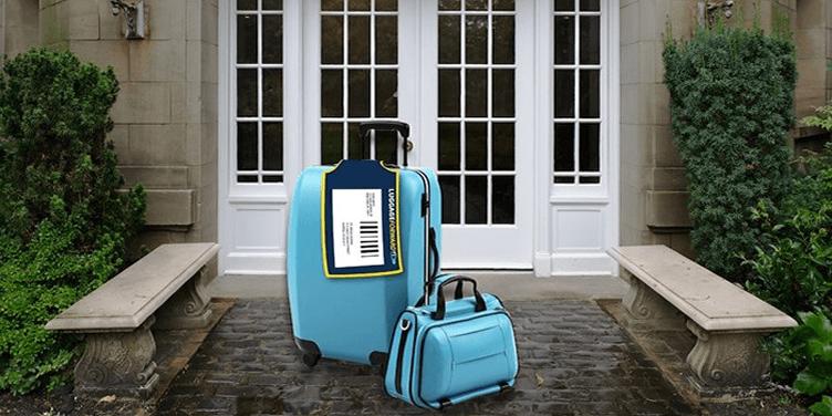 Após a execução de uma ordem de despejo duas malas azuis, uma grande e outra pequena, estão para o lado de fora de uma casa.
