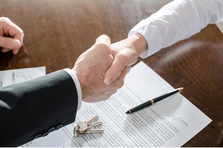 Corretor de imóveis lendo um contrato e fechando a venda. Aparecem somente as mãos com a chave da casa em cima do contrato.
