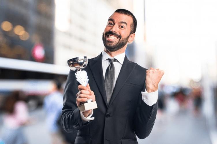 Corretor com um troféu na mão se achando o melhor do mercado imobiliário.