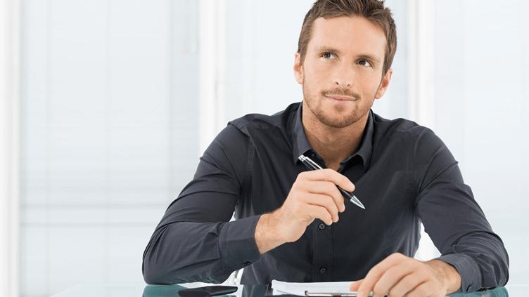 corretor de imóveis com uma caneta na mão e um papel sob a mesa pensando no seu plano de negócios.