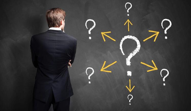 Corretor de imóveis olhando para um quadro negro com vários pontos de interrogação. Para descobrir quais as perguntas o corretor de imóveis deve fazer ao cliente.
