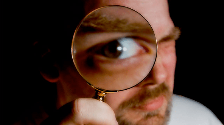 Corretor de imóveis com uma lupa bem perto de um olho. Para fazer perguntas para descobrir as necessidades do cliente que compra imóveis.