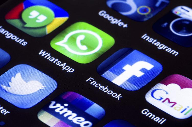 Perguntas que um Corretor deve Fazer ao Cliente no Atendimento Online. Mostra tela com fundo preto no celular em destaque ícones de midias sociais.