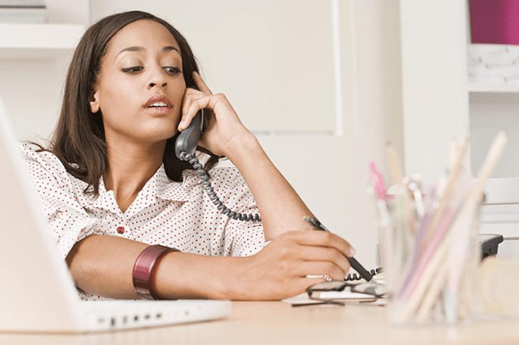 Perguntas que um Corretor de Imóveis deve Fazer ao Cliente em um Atendimento Telefônico. Corretora de imóveis com o telefone no ouvido atendendo um cliente e anotando suas respostas.