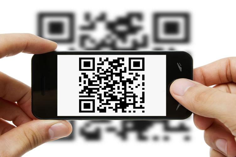 placa de vende-se com QR code. Na imagem, uma mão segurando o celular com o leitor de QR code