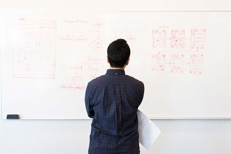 Dono da imobiliária olhando de frente para um planejamento rascunhado no quadro branco