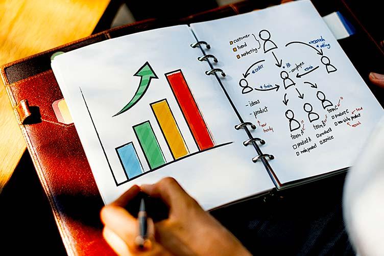 Corretor fazendo seu planejamento de negócios no caderno com gráficos e estratégias anotadas.