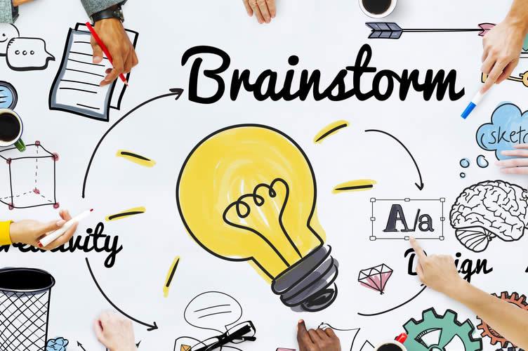 A palavra brainstorm ao centro, com várias mãos ao redor desenhando suas ideias.