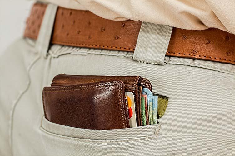 Bolso do consultor de imóveis com a carteira com dinheiro e cartões.