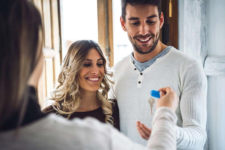 Corretor de imóveis entregando a chave do imóvel para um casal feliz pela aquisição.