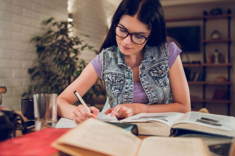 Mulher de cabelo escuro, usando óculos estudando para a faculdade de negócios imobiliários. Diversos livros sob a mesa.
