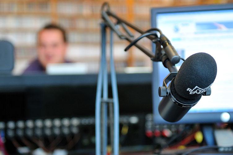 Foto do estúdio de uma rádio com um microfone a frente e de fundo um monitor e locutor.
