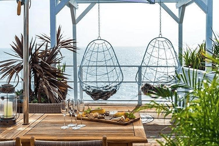 Espaço aconchegante de frente para o mar com a mesa posta do café da manhã. Boas imagens permitem conseguir mais reservas para aluguel de temporada