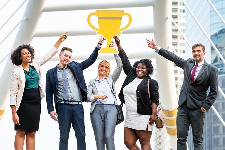 Gerente e equipe de corretores no alto de um prédio erguendo uma imagem de uma taça de campeão.