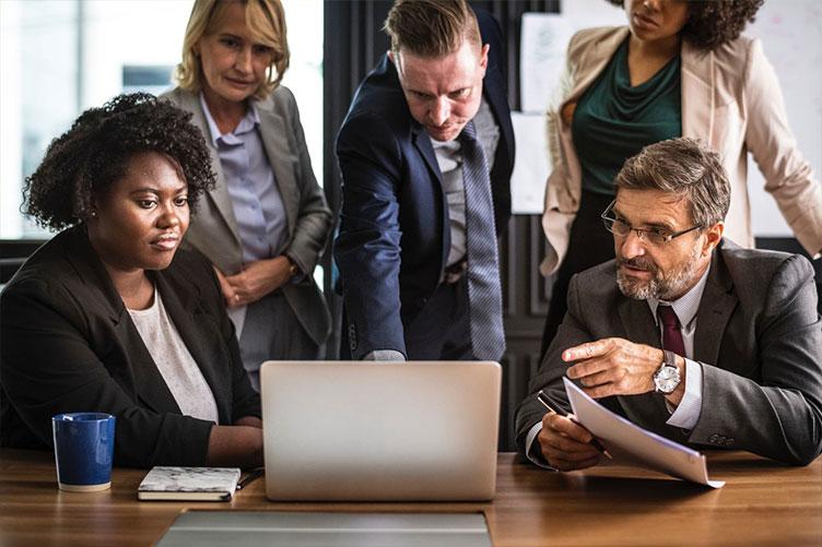 Equipe de corretores de imóveis olhando a tela do computador juntamente com o seu gerente