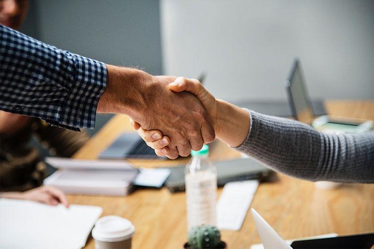 Corretora de imóveis cumprimentando o cliente após uma negociação bem sucedida.