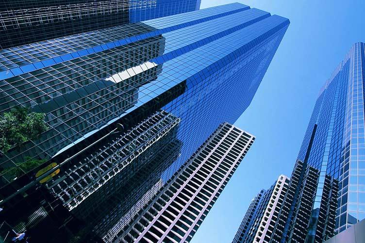 Condomínios envidraçados e imponentes vistos de baixo para cima com um céu azul ao fundo.
