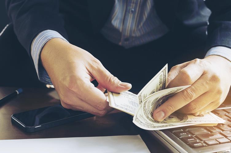 Transação monetária para vender imóveis no Brasil para estrangeiros. Homem contando notas de dólar.