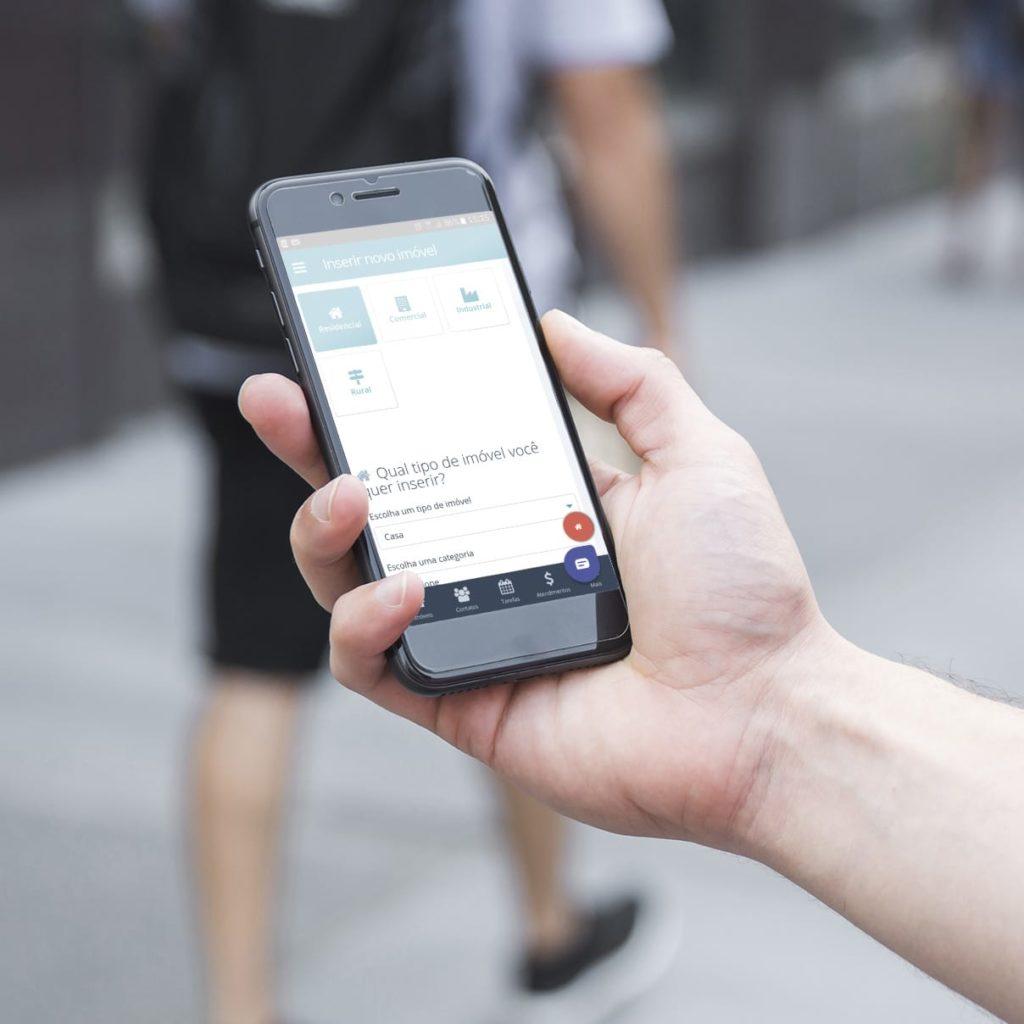 Pessoa segurando o celular utilizando o App do CRM Imobiliário Praedium