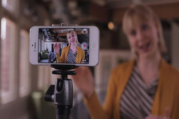 corretora de imóveis loira com um blaser amarelo gravando um vídeo imobiliário com seu Iphone apoiado em um tripé