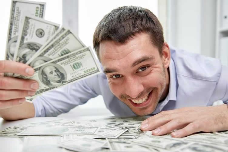 Corretor de Imóveis segurando alguns dólares e com mais um monte espalhados pela mesa. Corretor está com um enorme sorriso porque vale muito a pena ser corretor de imóveis.